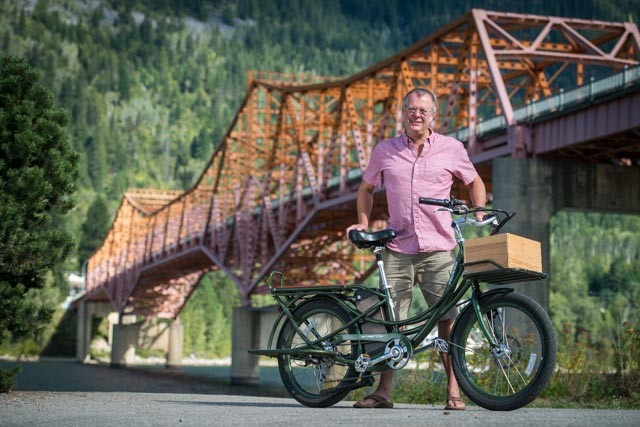 man standing beside the Big Orange Bridge in Nelson, BC with pedego electric bike