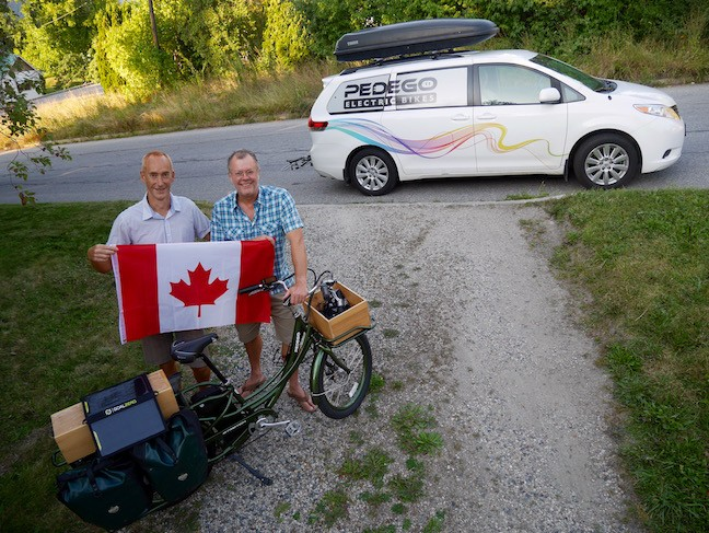 two men hold canadian flag by pedego electric bicycle