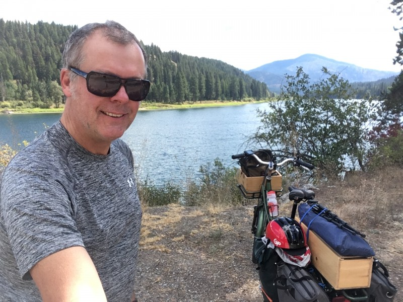 man stands beside Columbia River and a pedego stretch electric bike